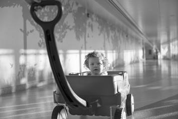 Toddler girl in red wagon