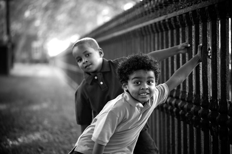 Brothers Playing On a Fence