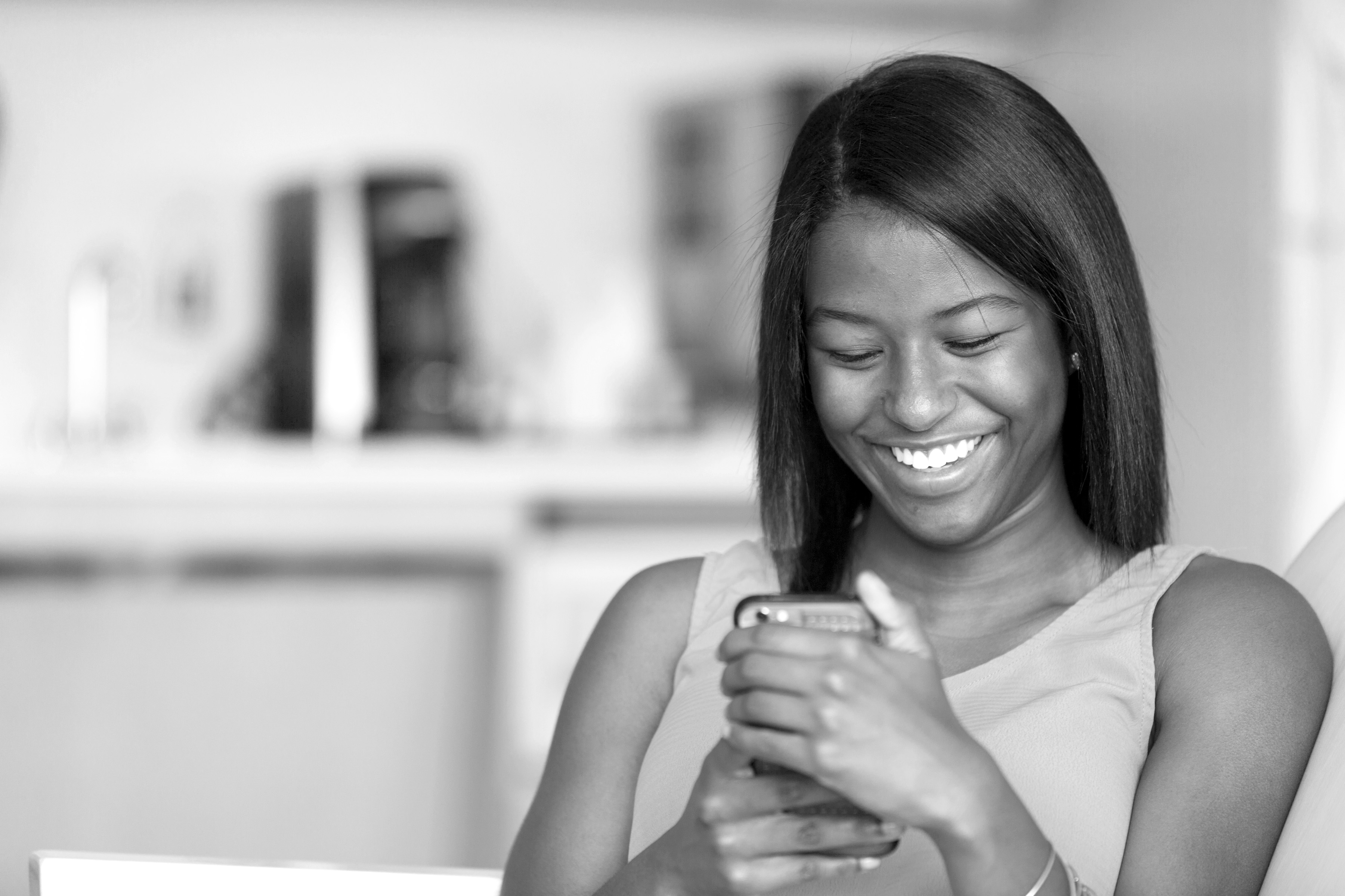 Teenage Girl Smiling and Looking at Her Cell Phone