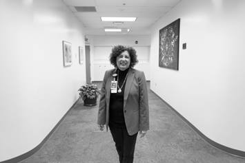 Lynn is smiling and standing in an empty hallway with art on the walls.