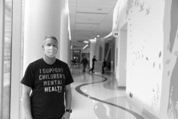 "Dr. Parker Huston standing in a hallway, wearing a shirt that says ""I Support Children's Mental Health"""