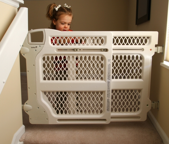 Small child behind baby gate