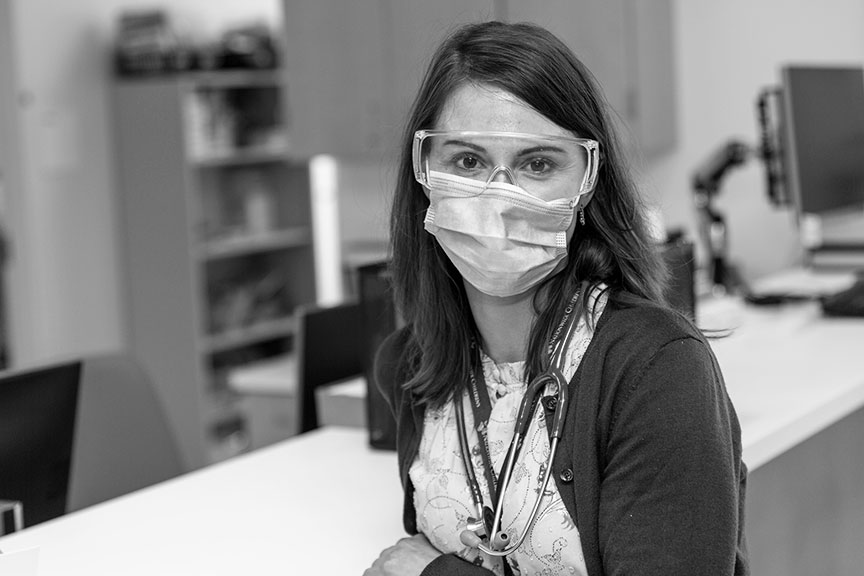 A primary care physician wearing a surgical mask and protective eyewear