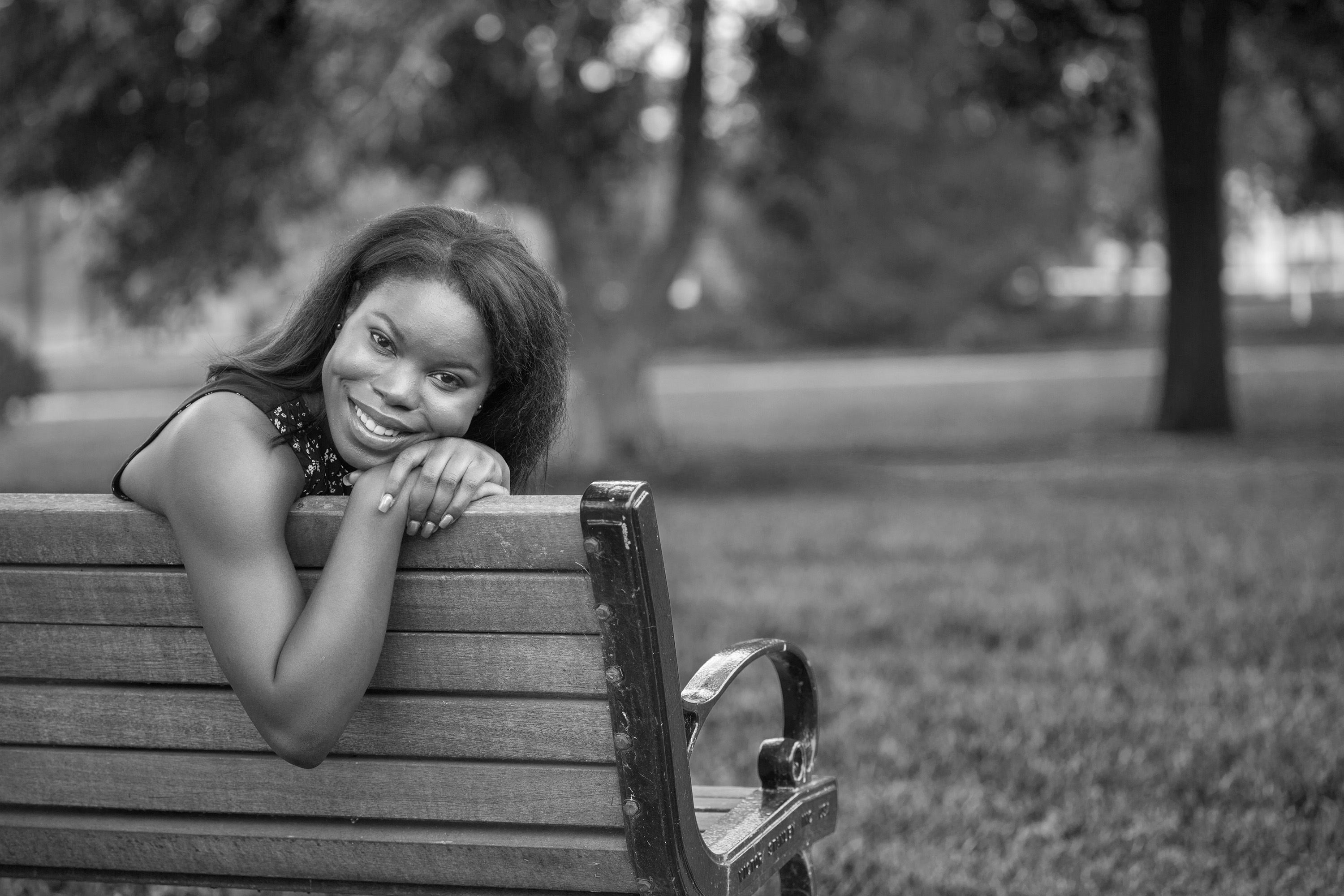 Young Woman Leaning Against Bench Smiling